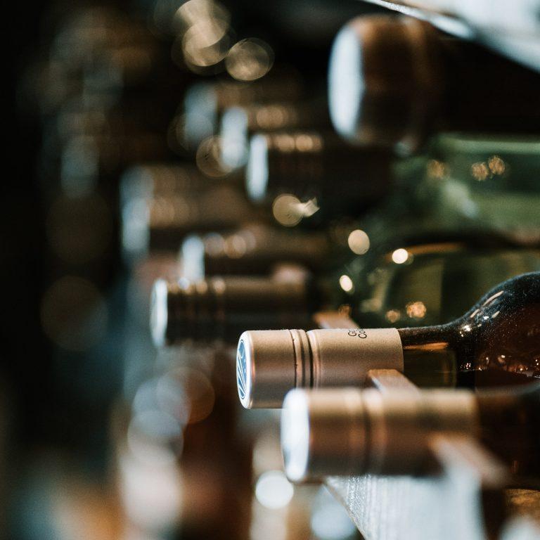 Vinícula com garrafas de vinhos deitadas, empilhadas